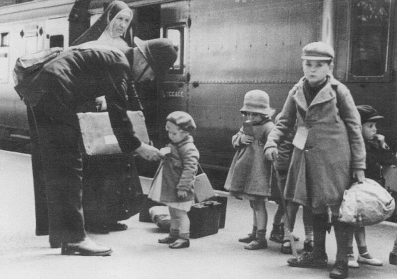 a policeman makes sure some evacuees are on the correct train out of london in 1940